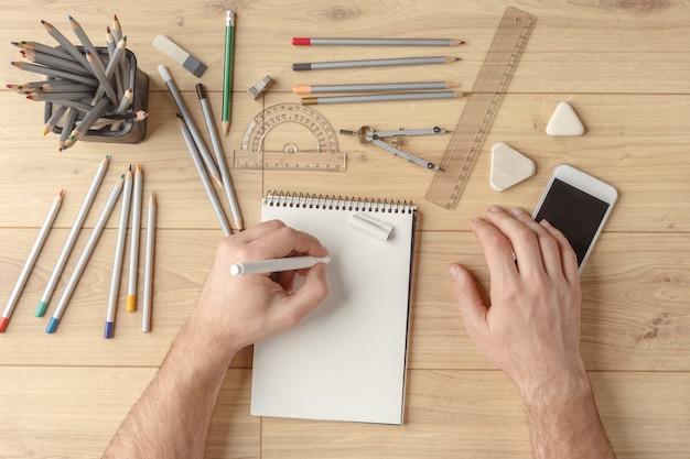 Le designer dessine un croquis dans un cahier sur une table en bois. papeterie. vue d'en-haut.