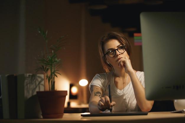 Designer femme sérieuse à l'aide d'une tablette graphique et d'un ordinateur