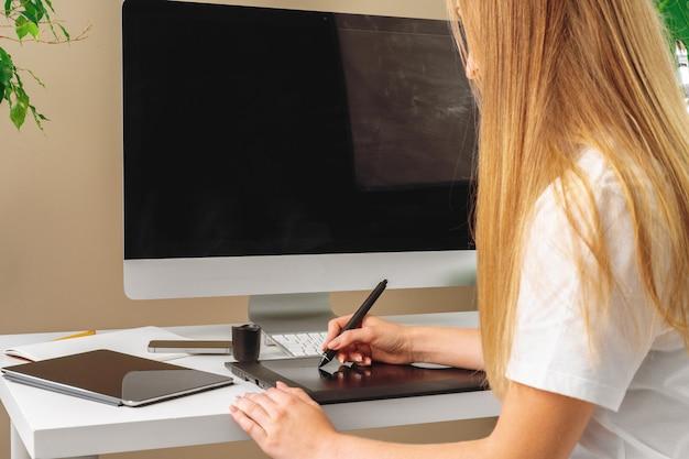 Designer femme travaillant au bureau et à l'aide d'une tablette graphique