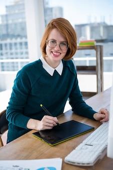 Designer hipster souriant, assis à son bureau, sur une tablette numérique