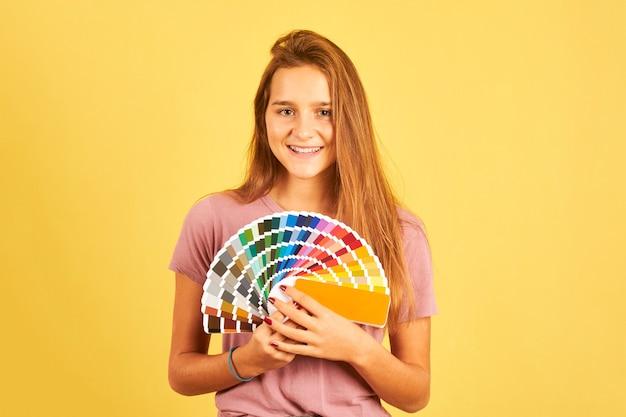 Designer d'intérieur femme tenant une palette de guide de couleurs isolé sur fond jaune