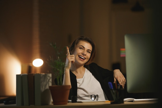 Designer de jeune femme heureuse assis dans le bureau la nuit