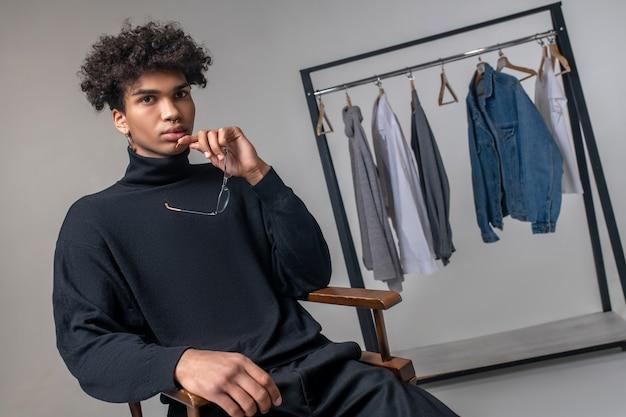 Designer. jeune homme afro-américain portant des vêtements noirs assis dans une salle d'exposition