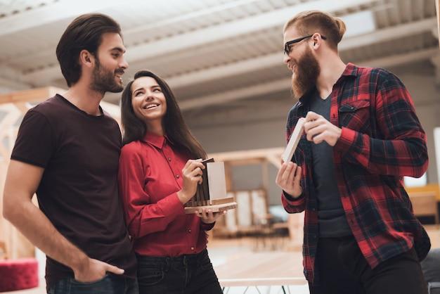 Le designer montre à un gars et à une fille des échantillons de bois.