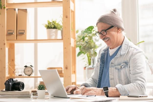 Designer ou photographe à succès mature en tenue décontractée assis par un bureau devant un ordinateur portable tout en surfant sur le net pour des idées créatives
