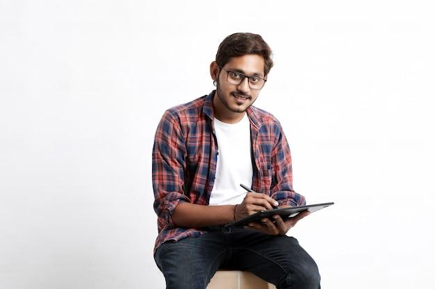 Designer professionnel indien utilisant une tablette graphique connectée à un smartphone avec un stylo numérique