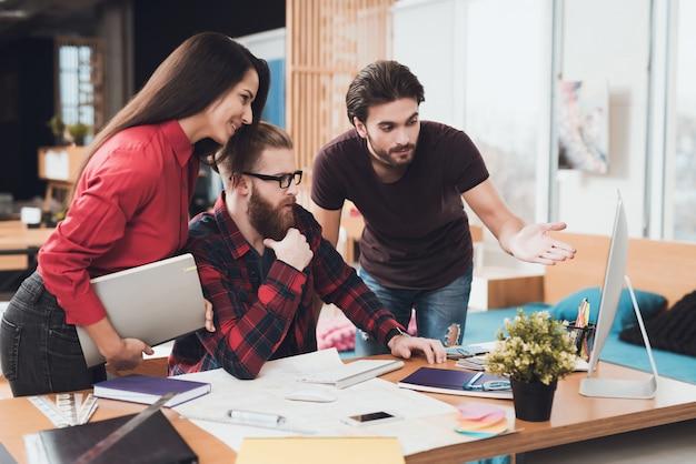 Designer et ses clients consultent l'écran de l'ordinateur.