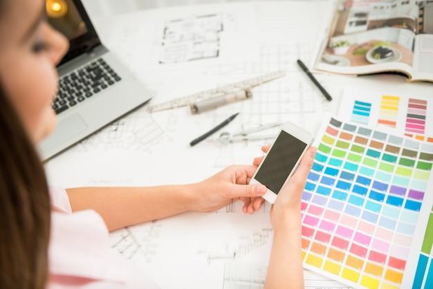 Designer travaillant au bureau à la maison et utilisant un téléphone.