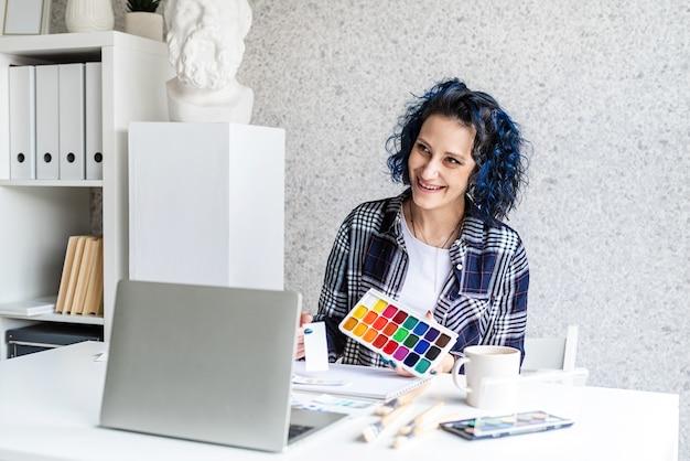 Designer travaillant avec des palettes de couleurs et un ordinateur portable dans son studio d'art
