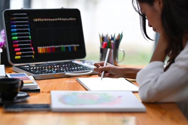 Designer travaillant avec une tablette numérique sur son lieu de travail créatif.