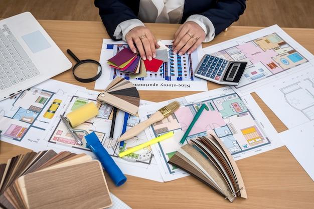 Le designer travaille au bureau avec des échantillons de couleurs, un ordinateur portable et un plan du bâtiment