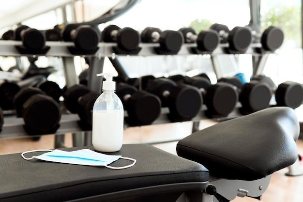 Désinfectant pour les mains et masque médical sur banc de gym