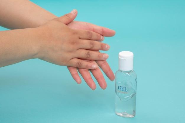 Désinfection des mains avec gel antibactérien sur fond bleu