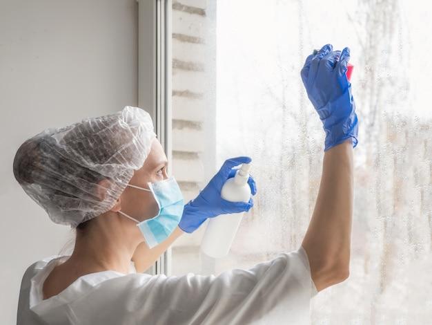 Désinfection par coronavirus. les gens dans la désinfection des fenêtres. docteur en gants de caoutchouc désinfecte les fenêtres avec un désinfectant et des éponges