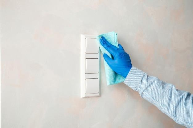 Désinfection des surfaces des interrupteurs. femme en caoutchouc bleu interrupteur d'éclairage propre avec un chiffon sur le mur par un chiffon humide. nouveau coronavirus covid 19 normal dans désinfecter, nettoyage à domicile. service de ménage propre.