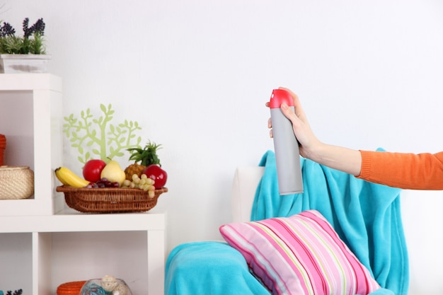 Désodorisant pulvérisé à la main sur l'intérieur de la maison