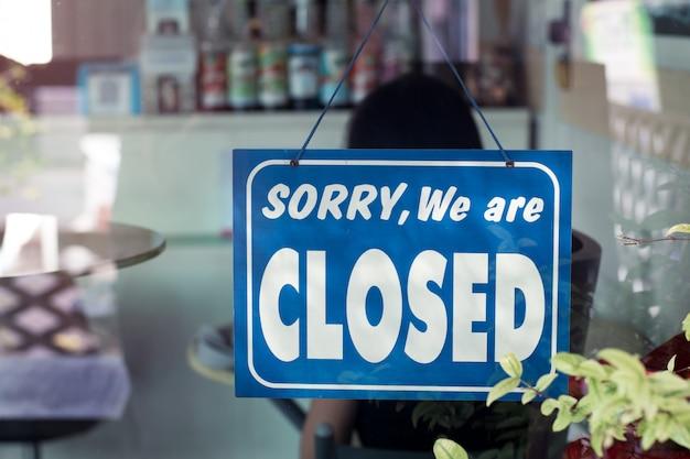 Désolé, nous sommes fermés signe suspendu à la porte du café.
