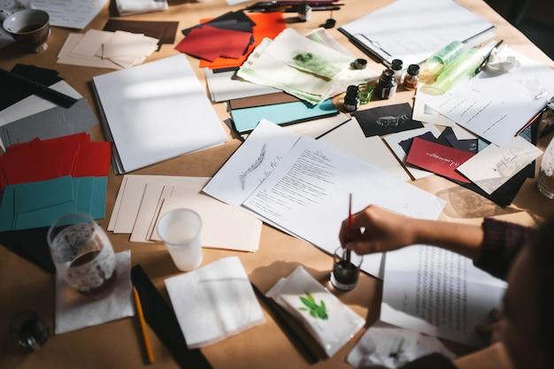 Désordre créatif sur la table d'un artiste qui pratique l'écriture avec un stylo-plume cours de calligraphie