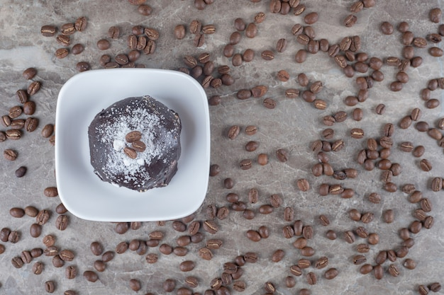 Désordre de grains de café autour d'un petit plateau avec un gâteau enrobé de chocolat sur une surface en marbre