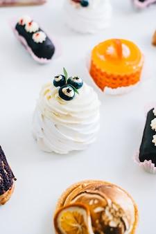 Dessert anna pavlova avec meringue et crème au fromage à l'intérieur, décoré de bleuets sur table avec d'autres gâteaux.