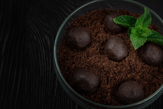 Dessert au chocolat de biscuits avec des morceaux de chocolat et de menthe sur un fond en bois foncé avec copie...