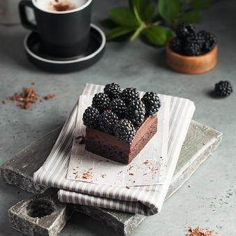 Dessert au chocolat décoré de mûres fraîches avec une tasse de café
