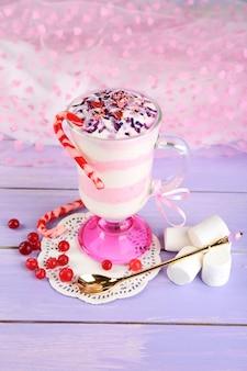 Dessert au lait de canneberge en verre, sur fond de bois de couleur