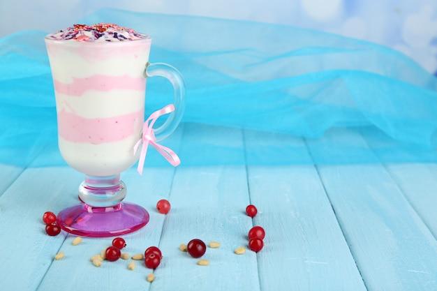Dessert au lait de canneberge en verre, sur table en bois de couleur, sur fond clair