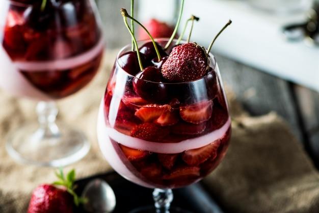 Dessert au lait avec cerise et fraise. gelée de lait. dessert yogourt. nourriture crue. panna cotta. dessert aux fraises. dessert aux petits fruits. mousse.