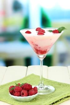 Dessert au lait de framboise dans un verre à cocktail, sur un espace lumineux