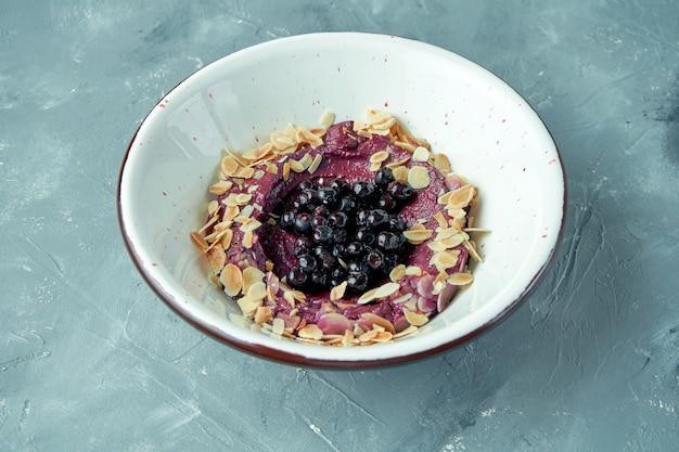 Dessert aux bleuets pour le petit déjeuner avec de la confiture et des amandes dans un bol blanc
