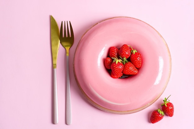 Dessert aux fraises maison fraîchement préparé avec une fourchette et un couteau d'or sur fond rose.