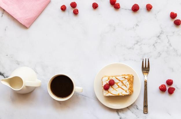 Dessert aux framboises et tasse de café noir sur marbre