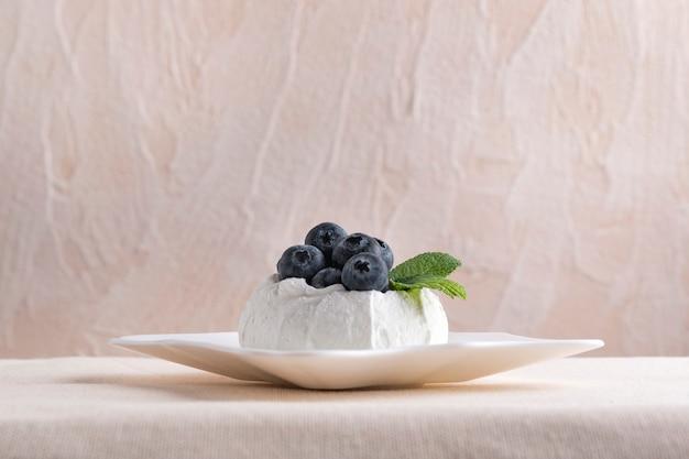 Dessert de baies sur soucoupe sur fond clair. meringue aux myrtilles fraîches.