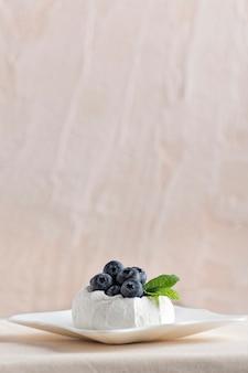 Dessert de baies sur soucoupe. meringue aux myrtilles fraîches. vue de côté, fond clair. cadre vertical.