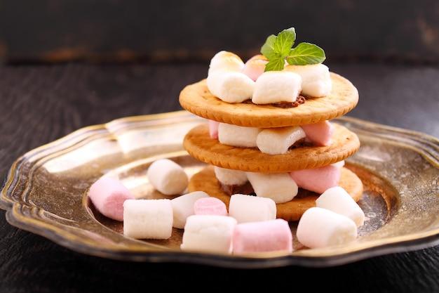 Dessert de biscuits, chocolat et guimauve sur fond bleu dans le décor de noël