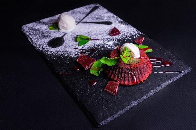 Dessert chocolat fondan à la menthe et crème glacée sur un bacground en bois. fondan au chocolat français exquis. petits gâteaux avec des décorations pour la saint valentin