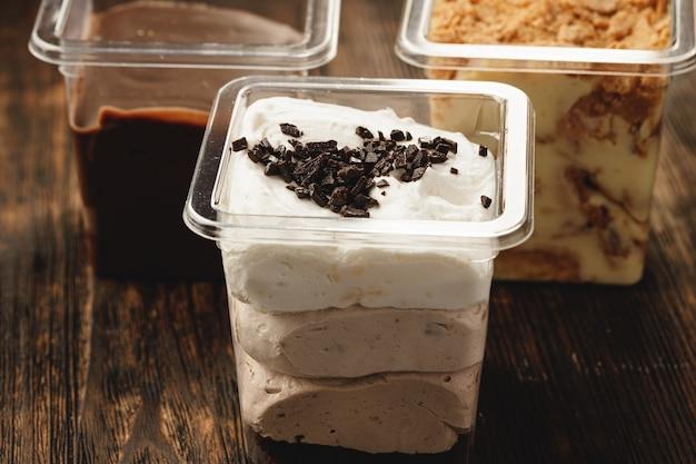 Dessert crémeux dans une boîte en plastique sur table en bois