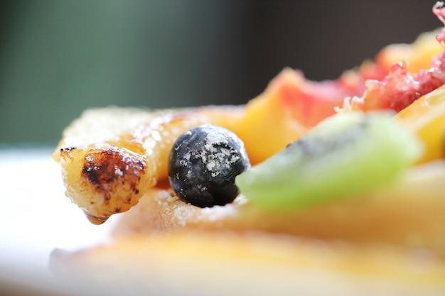 Dessert cuit gaufre aux fruits baies de raisin kiwo et crème glacée à la vanille