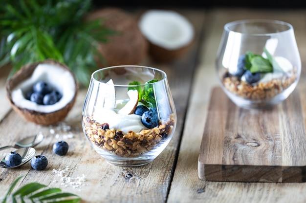Dessert diététique avec yaourt, granola et baies fraîches, gros plan, horizontal. ingrédients du petit déjeuner sain.