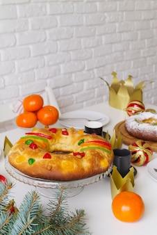 Dessert du jour de l'épiphanie sur la table avec fruits et couronne