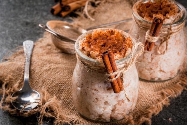 Dessert espagnol, sud-américain et mexicain. bouillie sucrée, riz au lait. riz au lait. en pots portionnés, décorés de cannelle et de sucre. sur une table en pierre sombre. espace copie