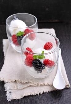 Dessert d'été avec des baies et de la crème glacée dans des verres sur un fond noir