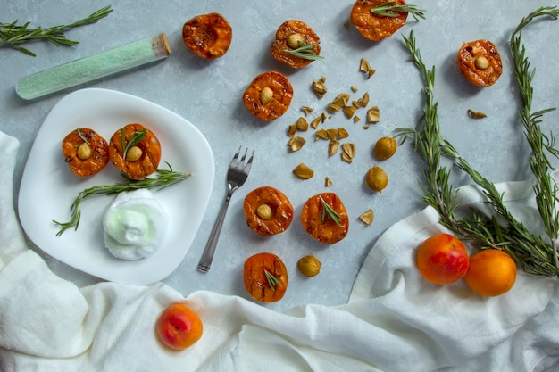 Dessert d'été. pêches grillées mûres avec noyaux d'abricot et feuilles de romarin sur bol blanc. mise à plat, vue de dessus