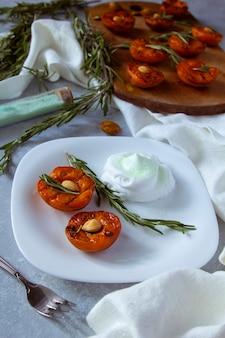 Dessert d'été. pêches grillées mûres avec noyaux d'abricot et feuilles de romarin sur bol blanc.