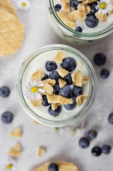 Dessert feuilleté sucré dans un verre avec myrtilles fraîches, crème fouettée, mascarpone, fromage cottage et biscuits biscuits ou gaufres sur fond clair.
