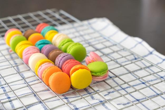 Dessert flou de dessert de macarons avec des tons pastel vintage sur une grille et un tissu