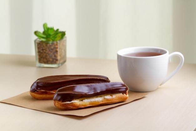 Dessert français traditionnel. délicieux éclairs avec crème anglaise, glaçage au chocolat et une tasse de thé chaud sur une table