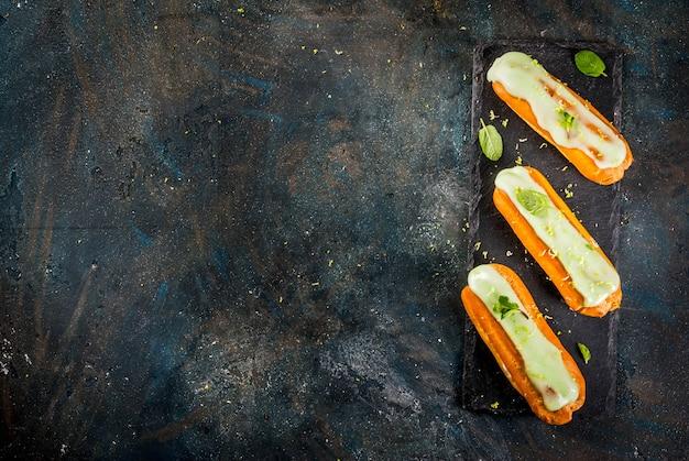 Dessert français traditionnel. mojito eclairs avec zeste de lime et feuilles de menthe, sur une surface bleu foncé, copie espace vue de dessus