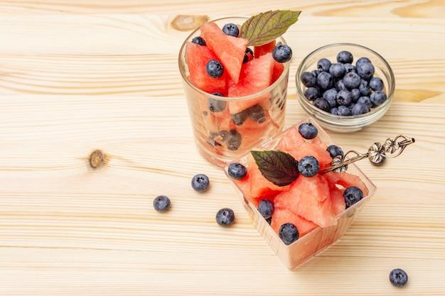 Dessert de fruits d'été frais. pastèque douce et myrtille, feuilles de basilic violet